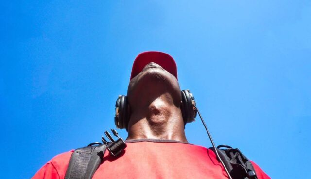 青空の下音楽を聴く男性