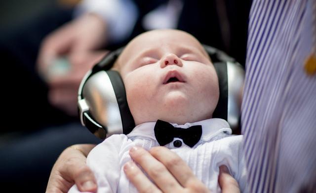 子供用ヘッドホンで音楽を聴きながらうとうとする赤ちゃん