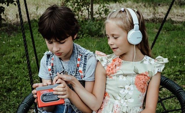 ヘッドホンで音楽を聴きながら、ゲームをする女の子と男の子