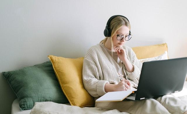 ヘッドホンをつけてパソコンをする女性