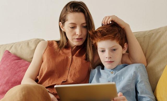 タブレットで遊ぶ少年と母親
