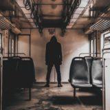 荒廃した電車内に佇む黒ずくめの人物
