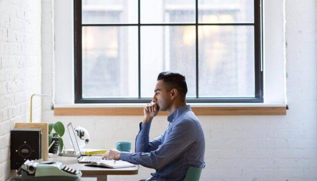 窓際で仕事する男性