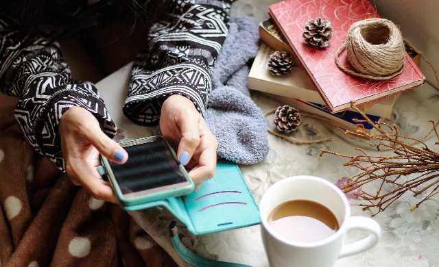 コーヒー飲みながらスマホ見てる女の人