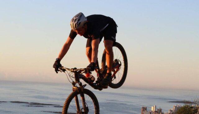 海辺を自転車で走行する男性