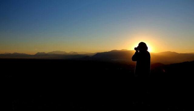 サンセットの写真を撮る男の人