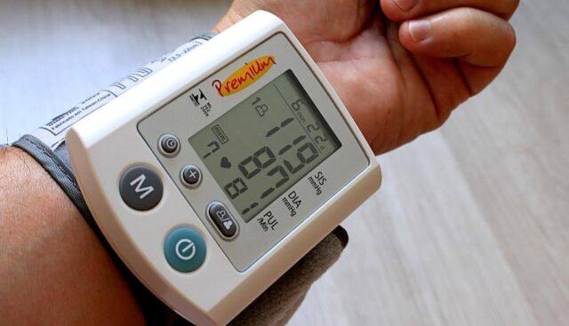 血圧計を腕につけている