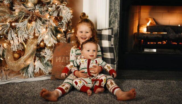クリスマスツリーの前に座る子供たち