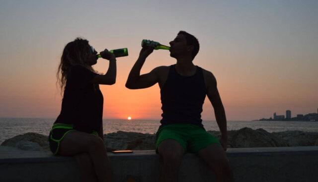 ビーチでビールを飲むカップル