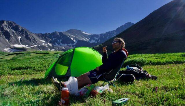山とテントでリラックスする男